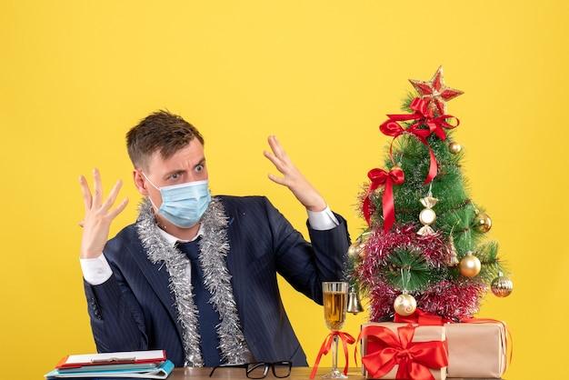 Vista frontal del hombre de negocios enojado sentado en la mesa cerca del árbol de navidad y presenta en la pared amarilla