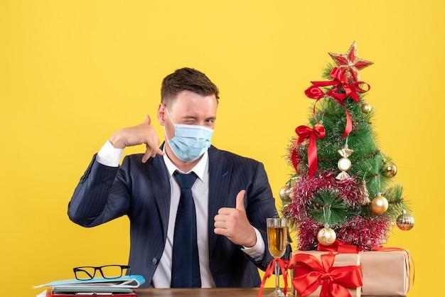 Vista frontal del hombre de negocios haciendo gesto de llamarme teléfono sentado en la mesa cerca del árbol de navidad y regalos en amarillo