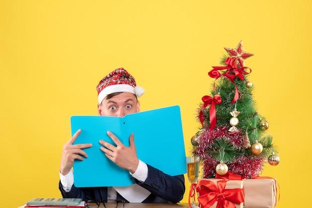 Vista frontal del hombre de negocios con los ojos abiertos sentado en la mesa cerca del árbol de navidad y presenta en amarillo