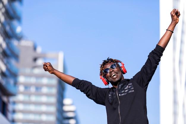 Vista frontal de un hombre negro con ropa casual y gafas de sol de pie en la calle mientras usa auriculares para escuchar música en un día soleado