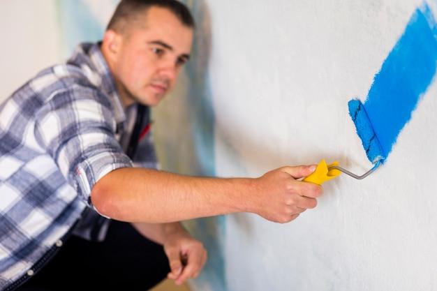 Vista frontal del hombre pintando una pared