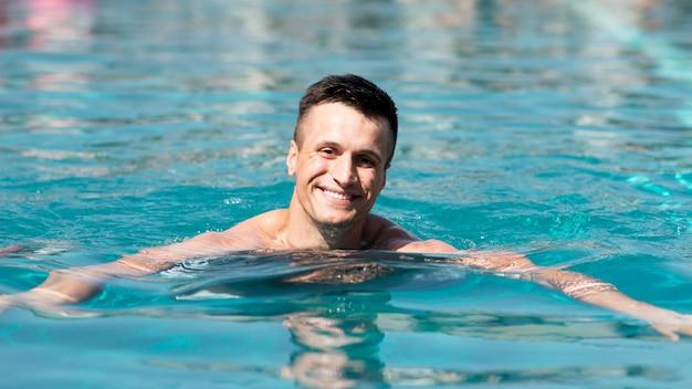 Vista frontal del hombre en la piscina