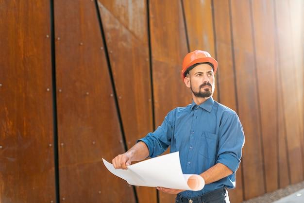 Vista frontal del hombre con plan de construcción