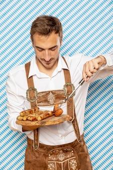 Vista frontal del hombre con plato de salchichas alemanas