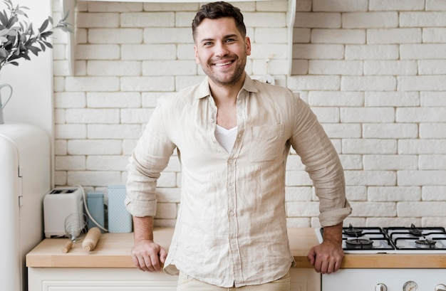 Vista frontal hombre posando en la cocina