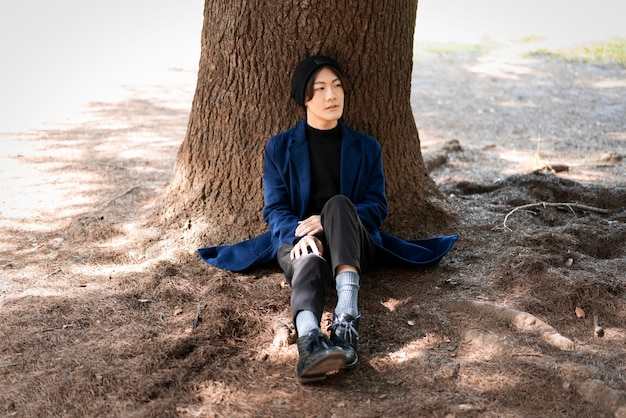 Vista frontal del hombre posando en el parque cerca del árbol