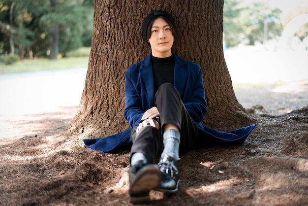 Vista frontal del hombre posando en el parque contra el árbol