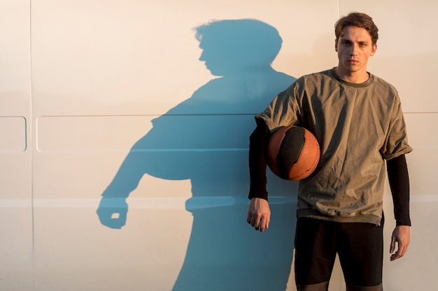 Vista frontal hombre posando con una pelota de baloncesto