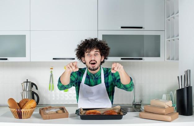 Vista frontal del hombre preguntándose de pie detrás de la mesa con pasteles recién horneados y apuntando hacia adelante en la cocina blanca