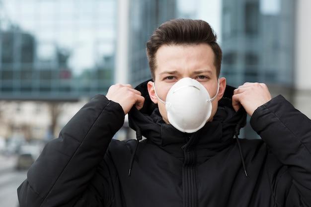 Vista frontal del hombre que llevaba una máscara médica afuera
