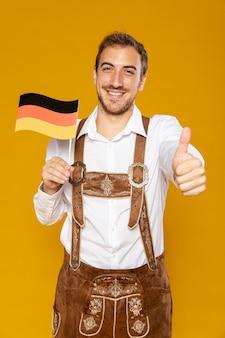 Vista frontal del hombre que sostiene la bandera alemana