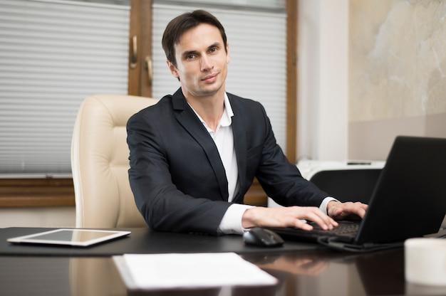Vista frontal del hombre que trabaja en la computadora portátil