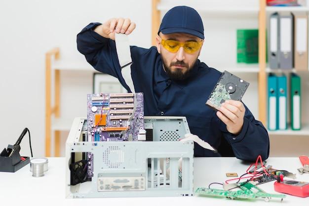 Vista frontal hombre reparando una computadora