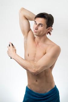 Vista frontal hombre rociando desodorante