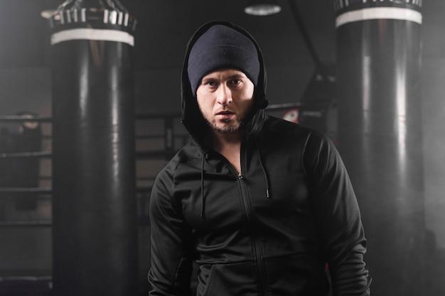 Vista frontal del hombre en ropa deportiva en el centro de entrenamiento de boxeo