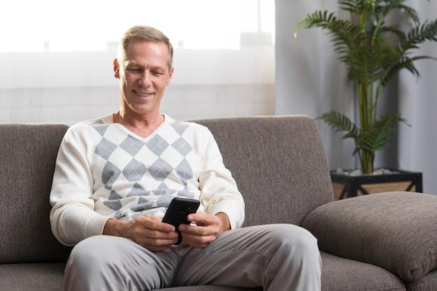 Vista frontal del hombre sentado en el sofá