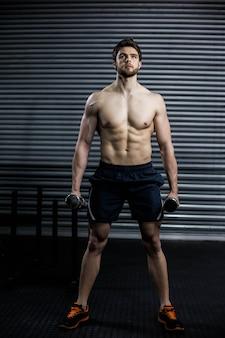 Vista frontal del hombre serio levantando peso en el gimnasio crossfit