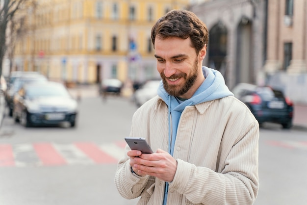 Vista frontal del hombre sonriente al aire libre en la ciudad con smartphone