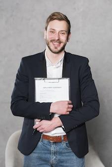 Vista frontal del hombre sonriente con contrato para nuevo trabajo