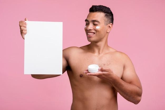Vista frontal del hombre sonriente con crema facial y cartel en blanco