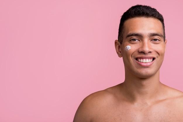 Vista frontal del hombre sonriente con crema en el rostro