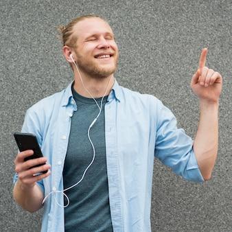 Vista frontal del hombre sonriente escuchando música en auriculares