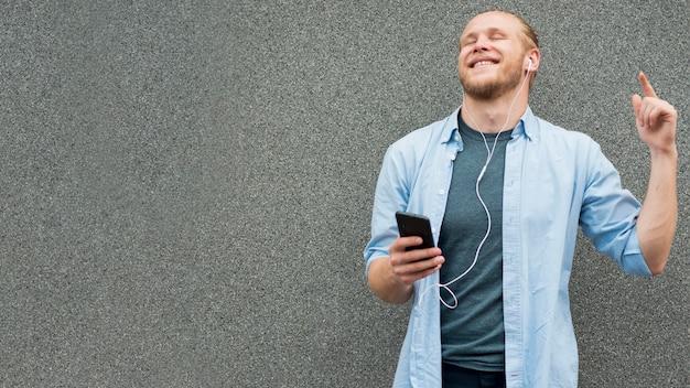 Vista frontal del hombre sonriente escuchando música
