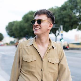 Vista frontal del hombre sonriente con gafas de sol en la ciudad