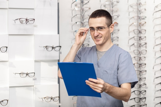 Vista frontal del hombre sonriente con gafas y sosteniendo el bloc de notas
