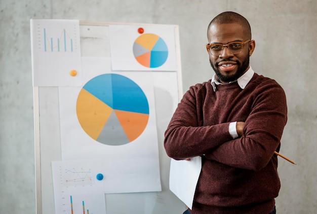 Vista frontal del hombre sonriente haciendo una presentación durante una reunión