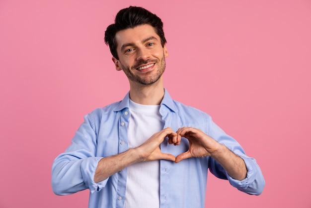 Vista frontal del hombre sonriente haciendo signo de corazón con sus manos
