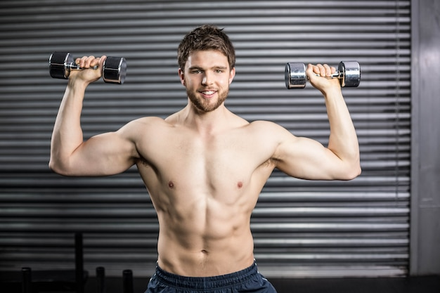 Vista frontal del hombre sonriente levantando peso en el gimnasio crossfit