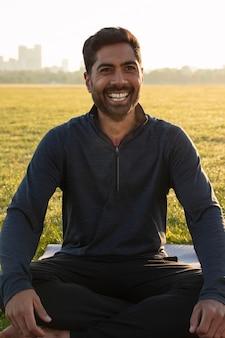 Vista frontal del hombre sonriente meditando al aire libre en la estera de yoga