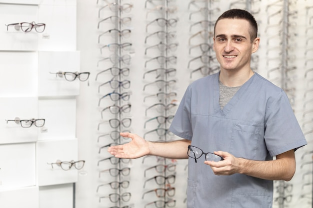 Vista frontal del hombre sonriente con par de anteojos en la mano