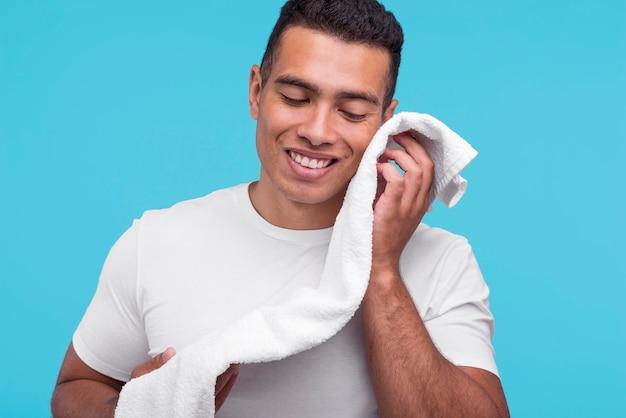 Vista frontal del hombre sonriente secándose la cara con una toalla limpia