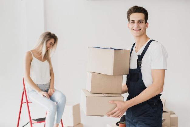 Vista frontal hombre sonriente sosteniendo cajas