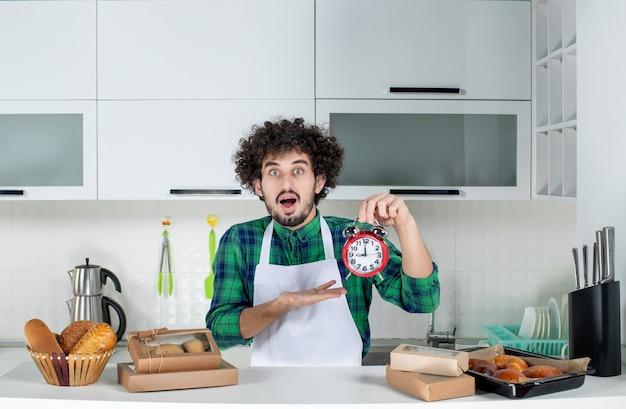 Vista frontal del hombre sorprendido de pie detrás de la mesa varios pasteles y apuntando el reloj en la cocina blanca