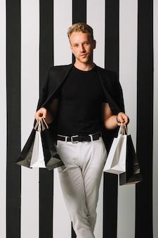 Vista frontal hombre sosteniendo bolsas de compras