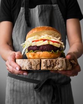 Vista frontal hombre sosteniendo una hamburguesa
