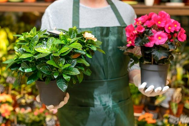 Vista frontal hombre sosteniendo macetas con flores