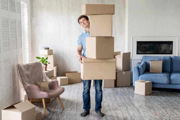 Vista frontal del hombre sosteniendo muchas cajas para mudarse