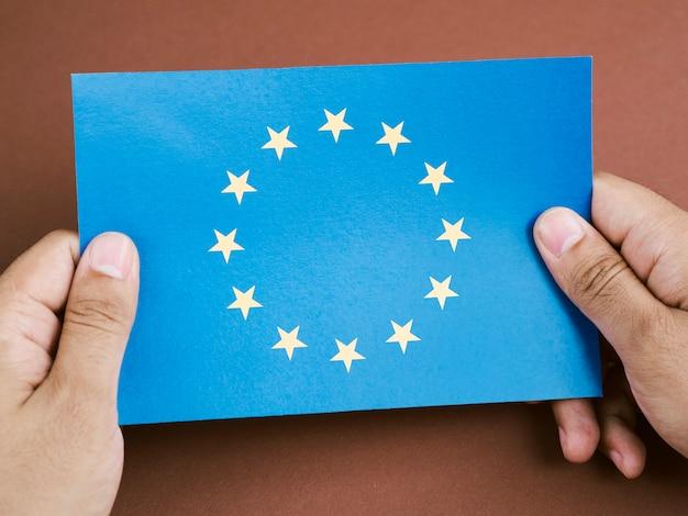 Vista frontal hombre sosteniendo una tarjeta con la bandera de la unión europea