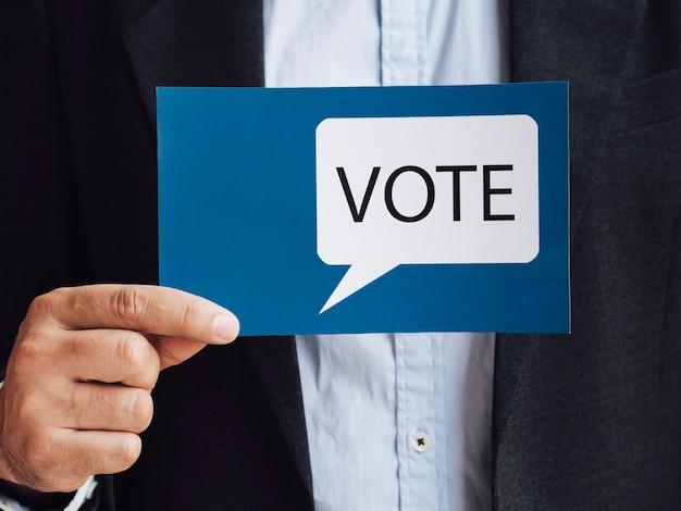 Vista frontal hombre sosteniendo una tarjeta de burbuja azul discurso de votación