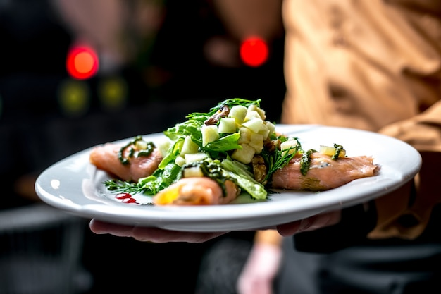 Vista frontal, un hombre sostiene un plato con ensalada de verduras con pescado rojo con verduras