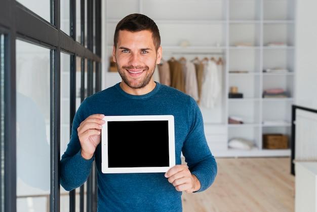 Vista frontal hombre con tableta que lo muestra a la cámara