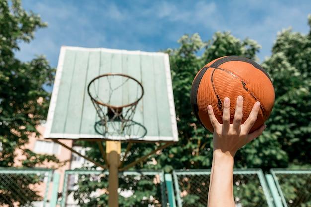 Vista frontal hombre tirando baloncesto en el aro