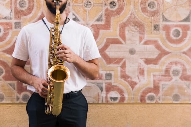 Vista frontal hombre tocando el saxo con fondo geométrico