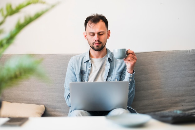 Vista frontal del hombre wotking en su computadora portátil