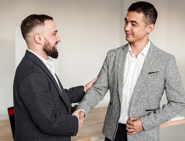 Vista frontal de hombres dándose la mano