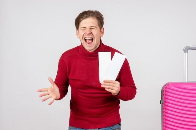 Vista frontal de los hombres jóvenes con billetes de avión en el escritorio blanco